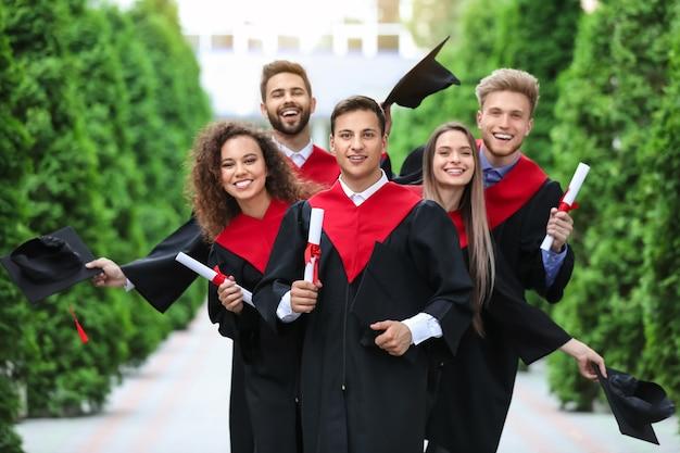 Étudiants heureux en robes de célibataire à l'extérieur