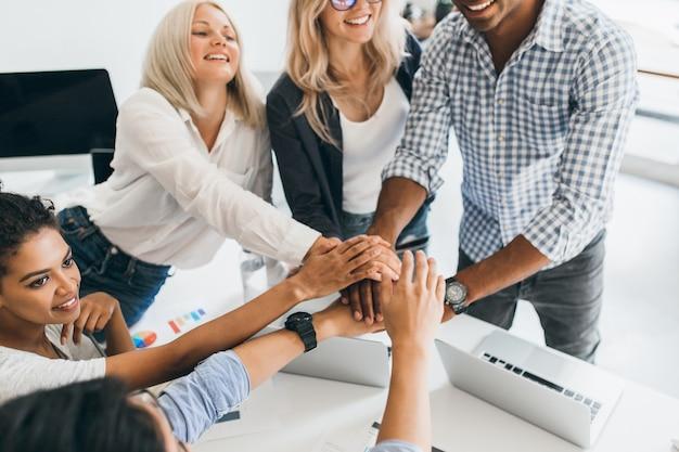 Des étudiants internationaux enthousiastes en tenue décontractée prêts pour le travail d'équipe. portrait intérieur d'une fille mulâtre heureuse aux cheveux bouclés tenant par la main avec une dame européenne et un jeune homme africain au bureau.