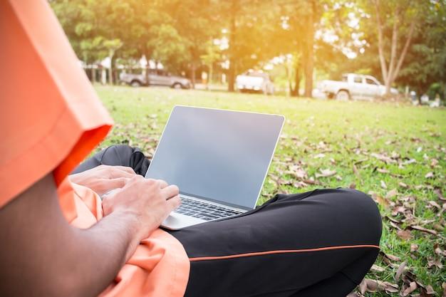 Étudiants jeune homme assis dans le parc sur l'herbe verte avec ordinateur portable