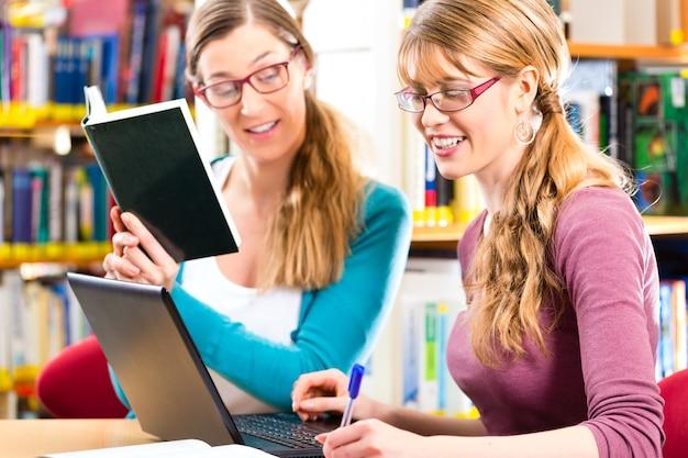 Étudiants - jeunes femmes en bibliothèque avec ordinateur portable et livre d'apprentissage en groupe