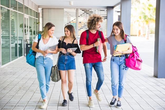 Des étudiants joyeux qui communiquent après les cours