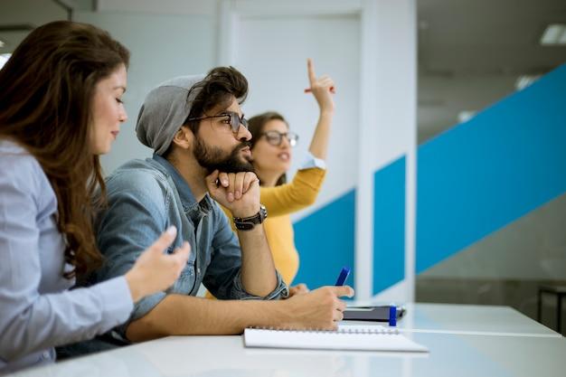 Étudiants levant la main pour répondre à la question lors de l'atelier de formation