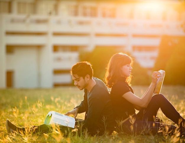 Les étudiants lisant à l'extérieur et le beau temps.