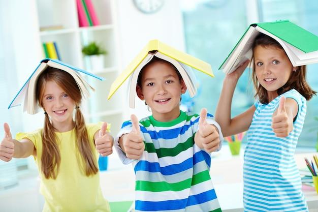 Les étudiants avec des livres ouverts sur la tête