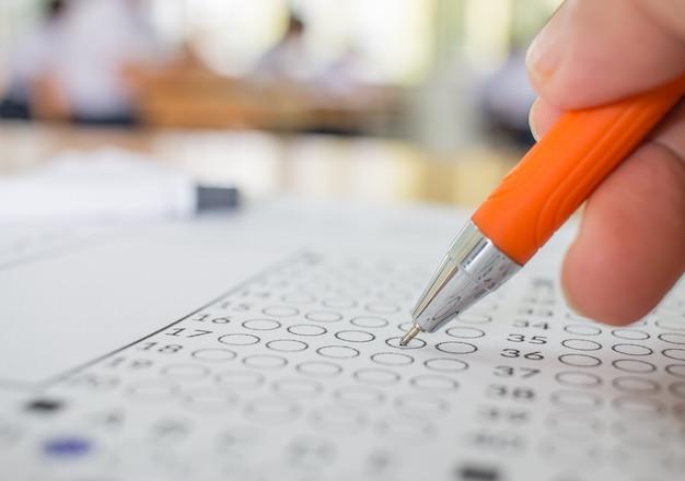 Les étudiants main testant l'examen avec un stylo