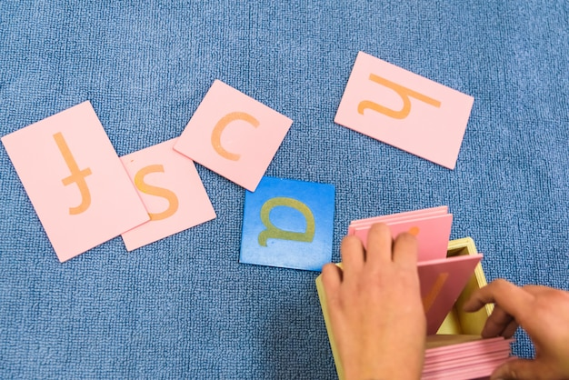 Étudiants manipulant du matériel de montessori dans une école sur un tapis pendant un cours.