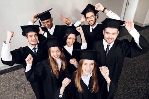 Les étudiants en manteaux sont heureux qu'ils terminent leurs études