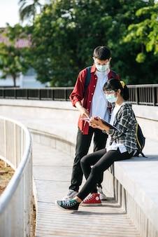Les étudiants masculins et féminins portant des masques s'assoient et lisent des livres dans les escaliers