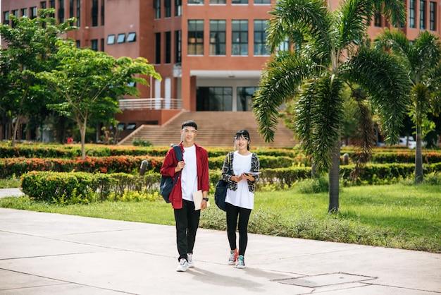 Les étudiants masculins et féminins portent un visage chill et se tiennent devant l'université.