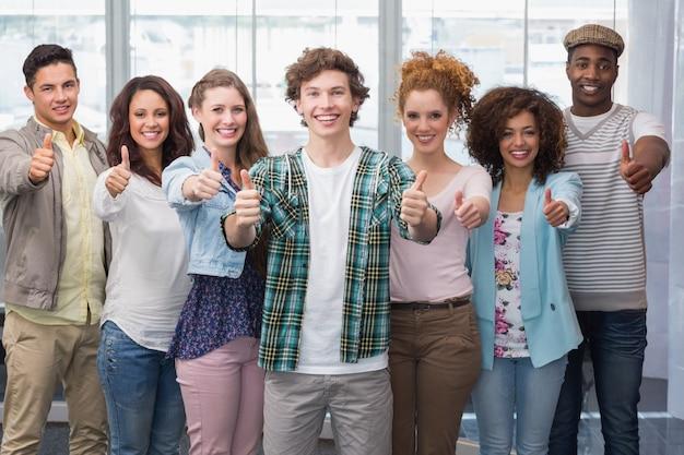 Étudiants de mode souriant à la caméra ensemble