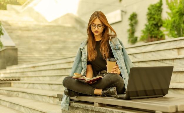 Étudiants modernes. apprentissage à distance. jeune fille hipster lit un livre assis sur un banc avec un ordinateur portable et boit du café