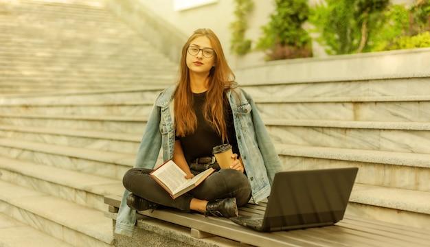 Étudiants modernes. apprentissage à distance. jeune fille hipster lit un livre assis sur un banc avec un ordinateur portable