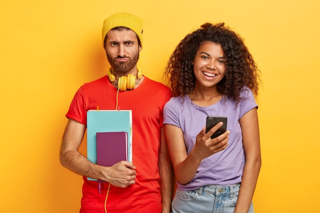 Les étudiants multiethniques passent du temps libre après les cours ensemble. triste étudiant de première année fatigué porte un chapeau, un t-shirt rouge, tient un journal et un cahier