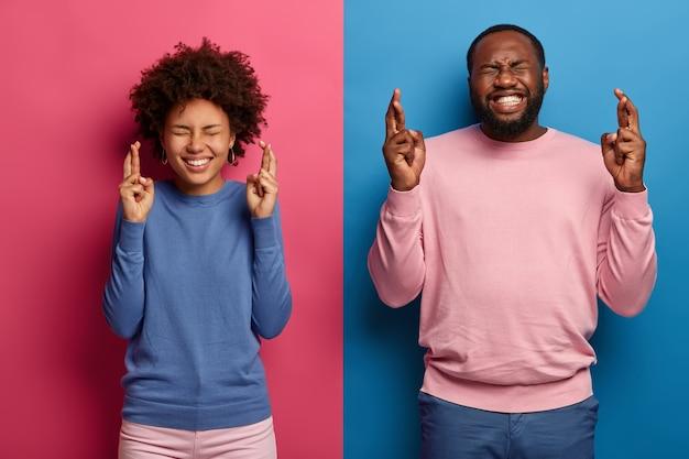 Des étudiants noirs heureux se croisent les doigts attendent les résultats de l'examen, prient pour obtenir la meilleure note