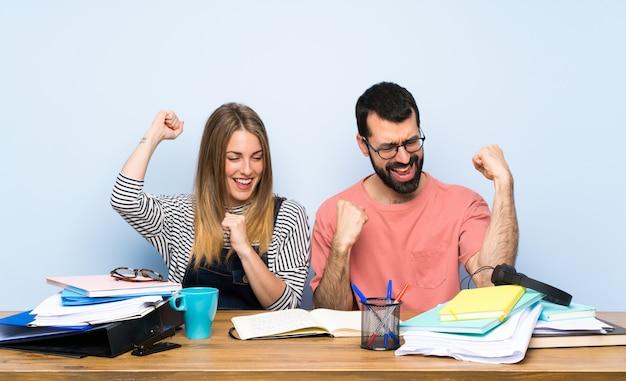 Étudiants avec de nombreux livres célébrant une victoire
