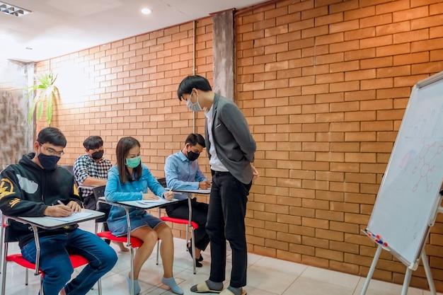 Les étudiants passent des examens pour collecter les notes à la fin du semestre et il y a un jeune enseignant qui supervise les examens dans la classe.