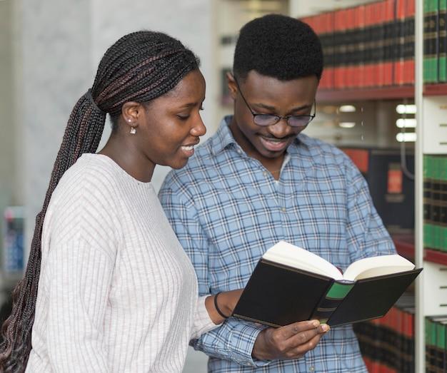 Étudiants de plan moyen lisant ensemble