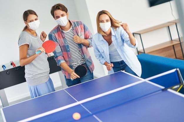 Étudiants portant des masques en jouant au tennis de table sur le campus