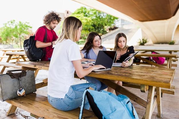 Étudiants qui étudient à table dans le parc