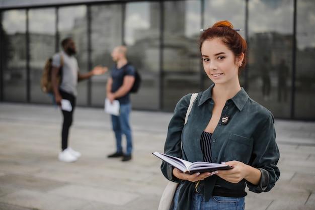 Étudiants souriants debout avec un bloc-notes