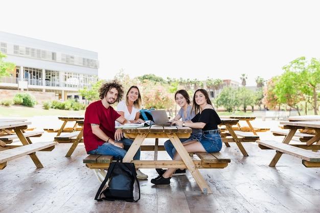 Étudiants souriants étudient ensemble à table