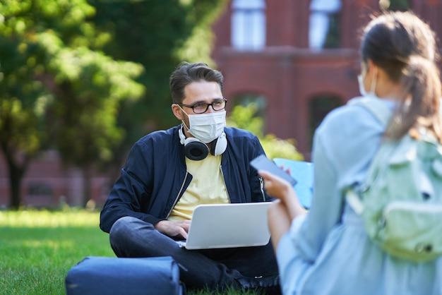 Étudiants traînant sur le campus portant des masques de protection et gardant la distance en raison de la pandémie de coronavirus