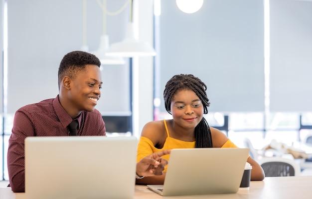 Étudiants universitaires africains utilisant un ordinateur portable ensemble.