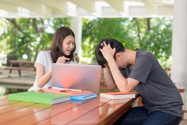 Étudiants universitaires avec cahier; préoccupé par les devoirs, le rapport doit être envoyé à l'instructeur