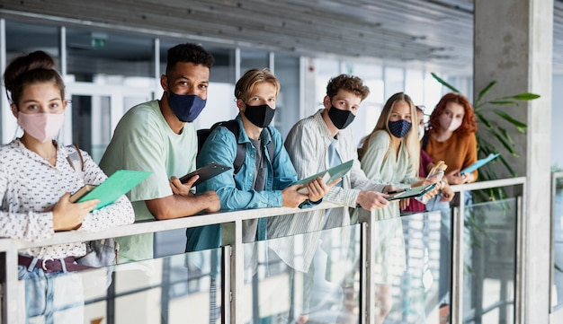 Étudiants universitaires debout et regardant la caméra à l'intérieur d'un coronavirus et retour au concept normal