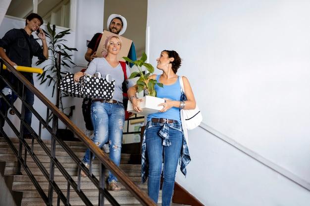 Des étudiants universitaires déménagent dans un nouvel appartement avec une boîte en carton et des trucs. colocataires amis premier jour sur le campus de l'université
