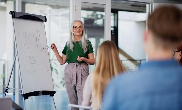 Étudiants universitaires avec enseignant étudiant à l'intérieur, concept de cours et de présentation.