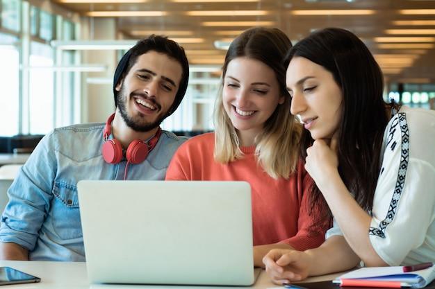 Étudiants universitaires utilisant un ordinateur portable dans la bibliothèque universitaire.