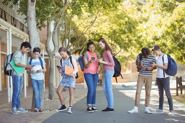 Étudiants utilisant un téléphone mobile sur la route du campus