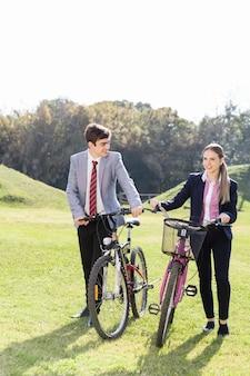 Les étudiants avec des vélos à pied dans la campagne
