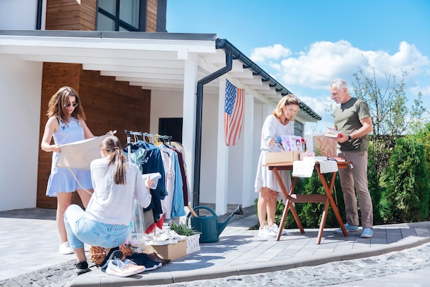 Etudiants en vente. deux étudiants à la mode moderne venant à la vente de garage dans leur quartier pour acheter des vêtements élégants