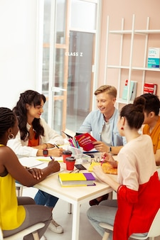 Étudier en groupe. bel homme blond gardant le sourire sur son visage en lisant un livre