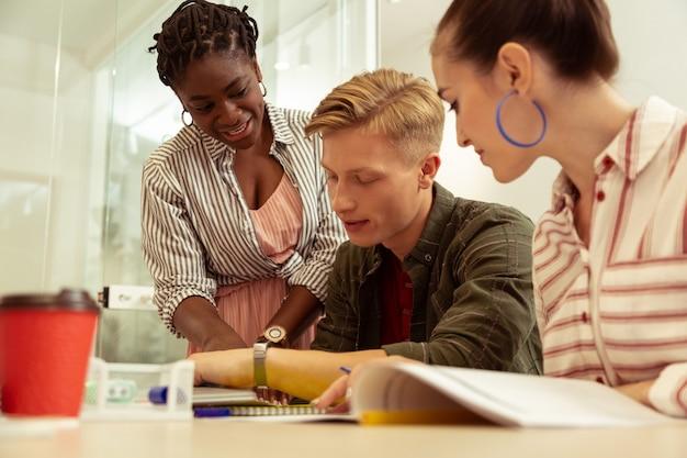 Étudiez avec plaisir. un homme blond gentil étant dans toutes les oreilles tout en accomplissant une tâche de grammaire