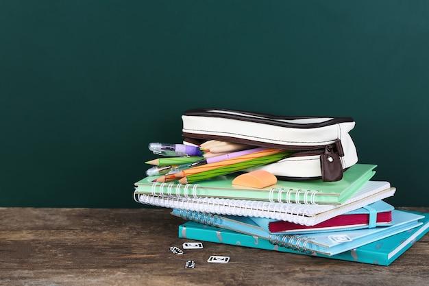 Étui à crayons avec divers articles de papeterie sur la vieille table en bois
