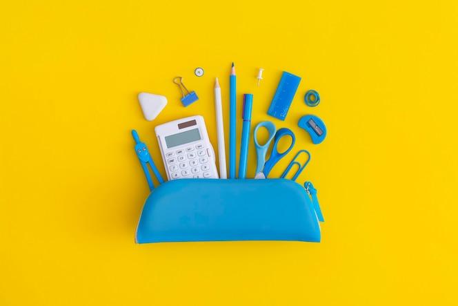 Étui à crayons avec papeterie scolaire sur fond jaune
