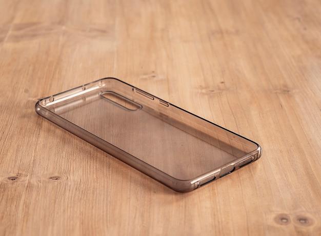 Etui mobile souple et transparent sur une table en bois