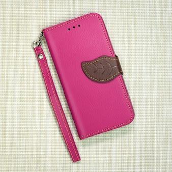 Etui de téléphone en cuir rose sur fond tissé. couverture de téléphone portable de mode.