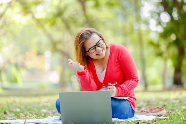 Euphorique, femme asiatique, recherche d'emploi avec un ordinateur portable dans un parc urbain en été