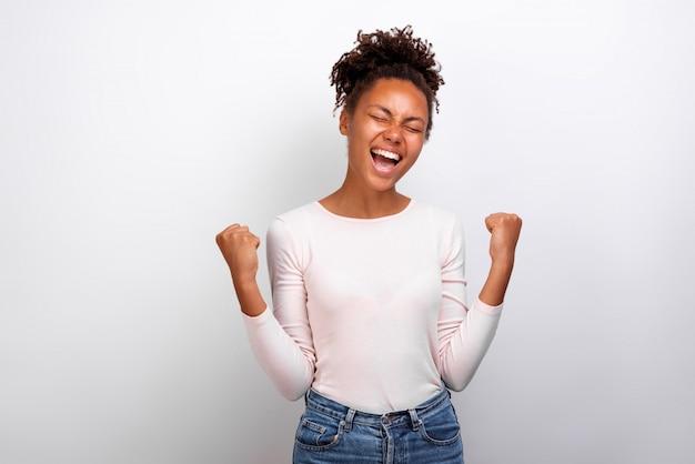 Euphorique femme leva les mains en geste de succès et hurla