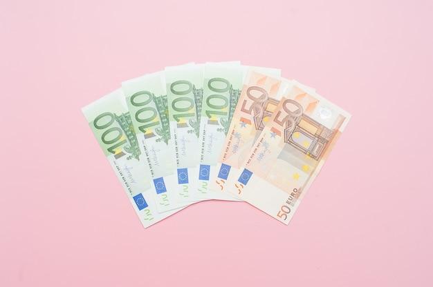 Euro argent en forme d'éventail. gros plan du billet de banque sur fond rose pastel.