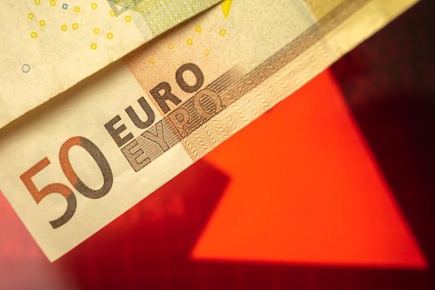 L'euro tombe sur les finances et les affaires, les billets en euros et le graphique boursier rouge avec la flèche vers le bas
