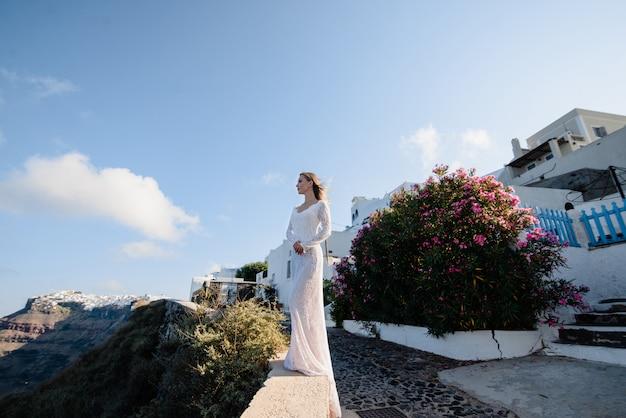 Europe grèce santorin vacances de voyage. femme regardant la vue sur la célèbre destination de voyage. élégante jeune femme vivant style de vie de jetset fantaisie portant une robe en vacances. vue imprenable sur mer et caldera