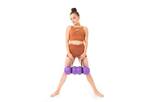 European brunette girl in a brown sports maillot de bain avec massage se dresse sur blanc