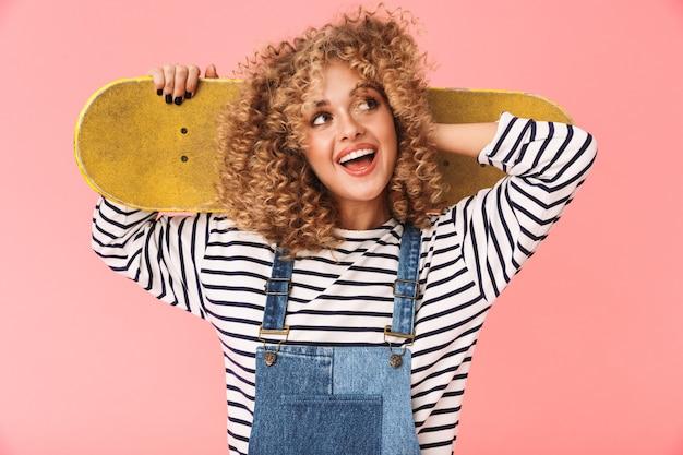 European curly girl 20s tenant la planche à roulettes en position debout