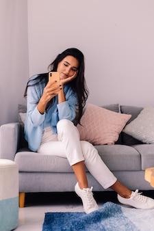 European fit brunette fashion blogger femme est assise sur le sol dans le salon près du canapé