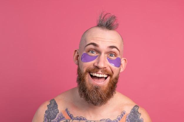 Européen bel homme topless tatoué barbu avec masque de patchs oculaires violet posant à la caméra sur rose